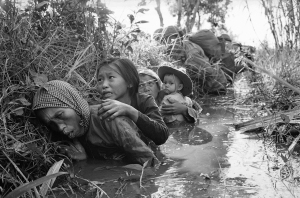 Women and children crouch in a muddy canal as they take cover from intense Viet Cong fire at Bao Trai, about 20 miles west of Saigon, Jan. 1, 1966. Paratroopers, background, of the U.S. 173rd Airborne Brigade escorted the South Vietnamese civilians through a series of firefights during the U.S. assault on a Viet Cong stronghold. (AP Photo/Horst Faas)
